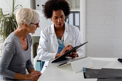 Older Black female doctor consulting with older white female patient