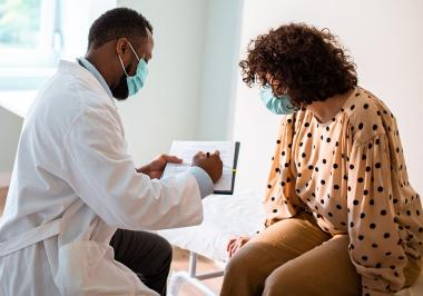 Doctor treating patient wearing face masks