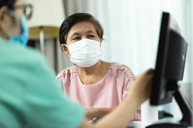 Older female patient consulting with physician in masks
